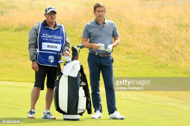 Robert Rock of England looks down the 18th hole with caddie Kyle Roadley during the final round of the AAM Scottish Open at Dundonald Links Golf...