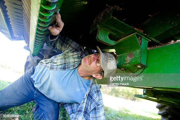 Robert Roden adjusts the tractor before harvesting a soy bean field on the RobNCin farm on September 29 2010 in West Bend Wisconsin The farm has...