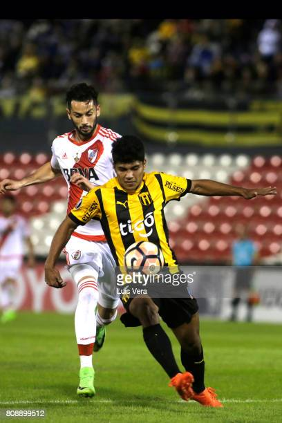 Robert Rojas of Guarani fights for the ball with Marcelo Larrondo of River Plate during a first leg match between Guarani and River Plate as part of...