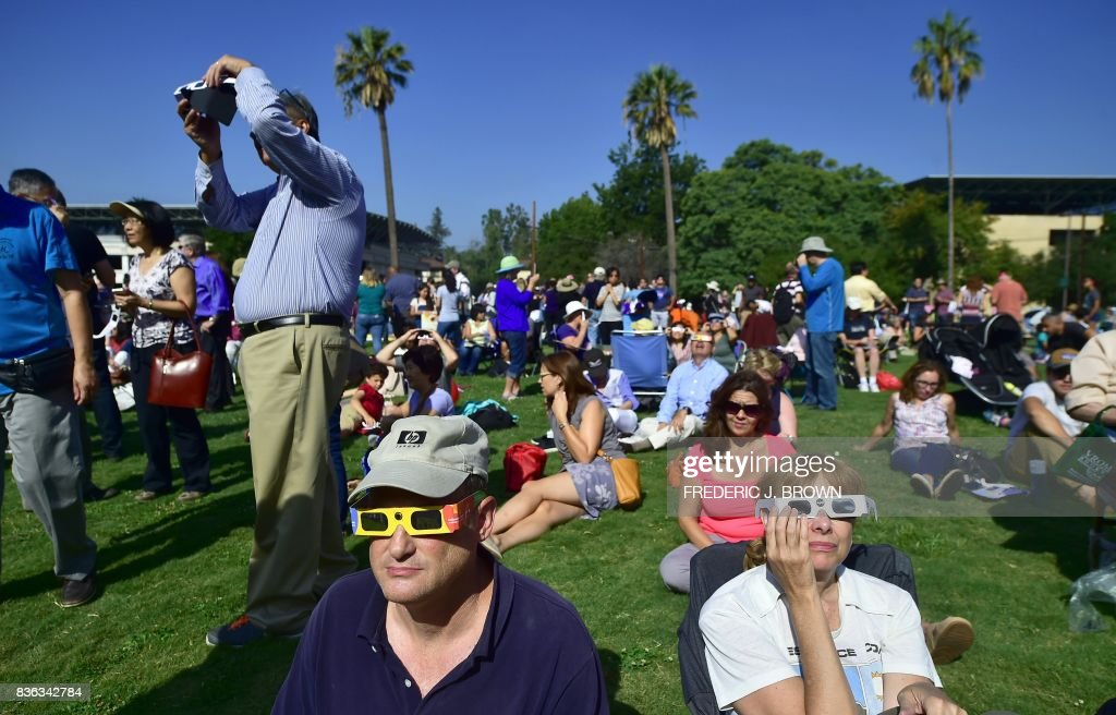 Robert Rubino (L) and Janice Rocker (R) wear solar eclipse glasses to view the partial eclipse from Beckman Lawn at Caltech in Pasadena, California on August 21, 2017. Emotional sky-gazers stood transfixed across North America Monday as the Sun vanished behind the Moon in a rare total eclipse that swept the continent coast-to-coast for the first time in nearly a century. /