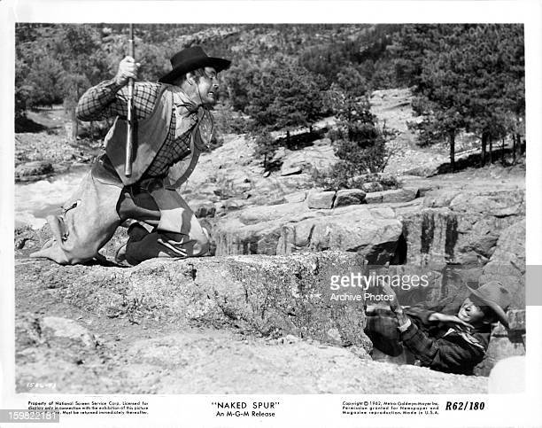 Robert Ryan and James Stewart fighting on side of cliff in a scene from the film 'The Naked Spur' 1953
