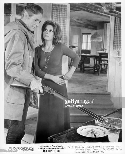 Robert Ryan placing his rifle on a plate while Lea Massari looking at him in a scene from the film 'And Hope to Die', 1972.
