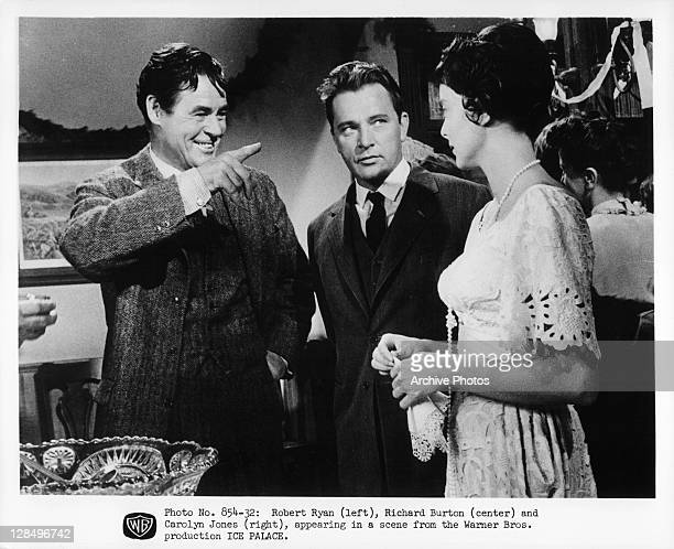 Robert Ryan Richard Burton and Carolyn Jones having conversation near punch bowl in a scene from the film 'Ice Palace' 1960