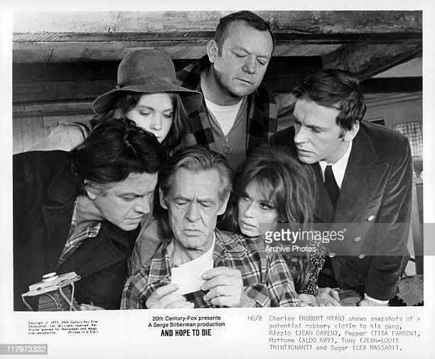 Robert Ryan showing a photograph to Jean Gaven Tisa Farrow Aldo Ray JeanLouis Trintignant and Lea Massari in a scene from the film 'And Hope to Die'...