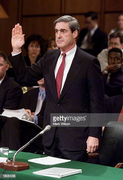 Robert S. Mueller III, President Bush''s choice to become director of the Federal Bureau of Investigation, raises his right hand while being sworn...