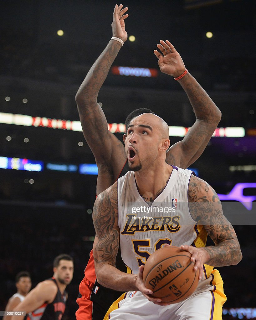 Robert Sacre #50 of the Los Angeles Lakers attempts against the Toronto Raptors at Staples Center on December 8, 2013 in Los Angeles, California.