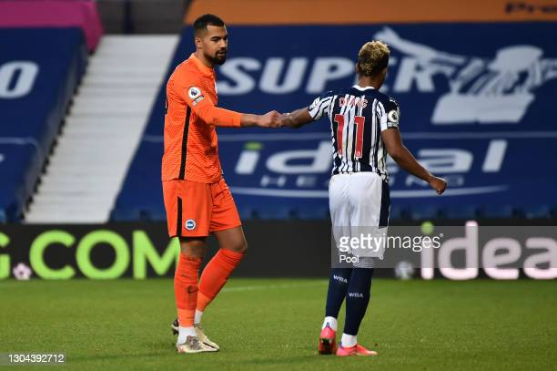 Robert Sanchez of Brighton and Hove Albion interacts with Grady Diangana of West Bromwich Albion following the Premier League match between West...