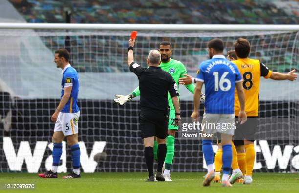 Robert Sanchez of Brighton and Hove Albion protests to Match Referee Jonathan Moss as team mate Lewis Dunk is shown a Red Card during the Premier...
