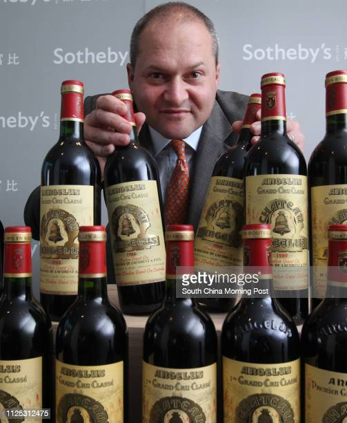 Robert Sleigh Sotheby's Senior Director Head of Wine Asia poses for a photo with wines from Chateau Angelus are seen at Sotheby's Hong Kong's media...