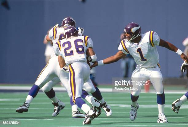Robert Smith of the Minnesota Vikings takes the handoff from quarterback Warren Moon against the New York Giants during an NFL football game...