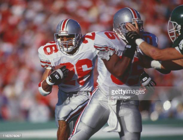 Robert Smith, Running Back for the Ohio State Buckeyes runs the ball against the Michigan State Spartans defense during their NCAA Big Ten conference...