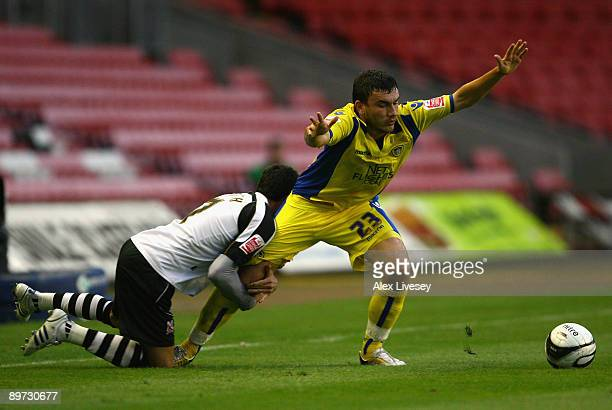 Robert Snodgrass of Leeds United is held back by Jeff Smith of Darlington during the Carling Cup First Round match between Darlington and Leeds...