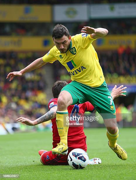 Robert Snodgrass of Norwich City is tackled by Goran Popov of West Bromwich Albion during the Barclays Premier League match between Norwich City and...