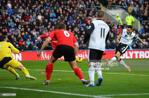 Robert Snodgrass of Norwich City shoots past goalkeeper David Marshall of Cardiff City to score their first goal during the Barclays Premier League...