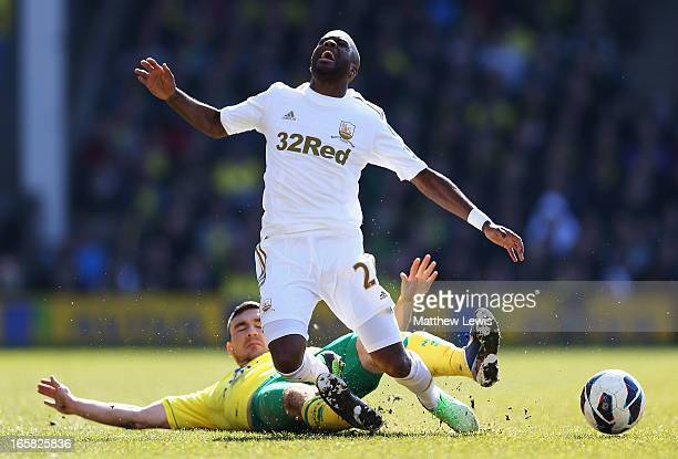 Robert Snodgrass of Norwich City tackles Dwight Tiendalli of Swansea City during the Barclays Premier League match between Norwich City and Swansea...