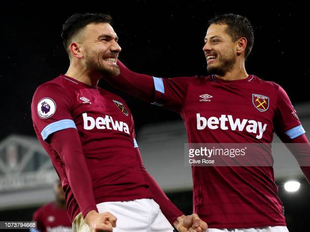Robert Snodgrass of West Ham United celebrates with teammate Javier Hernandez after scoring his team's first goal during the Premier League match...