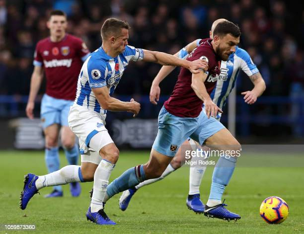Robert Snodgrass of West Ham United is challenged by Jonathan Hogg of Huddersfield Town during the Premier League match between Huddersfield Town and...