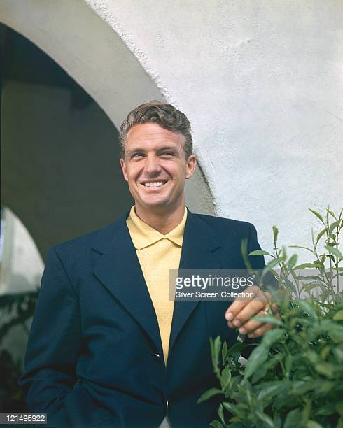 Robert Stack US actor wearing a dark blue jacket with a yellow polo shirt standing smiling beside a bush circa 1960