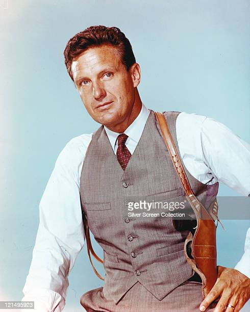 Robert Stack US actor wearing a grey waistcoat with a white shirt and a dark red tie with a tan leather holster over his shoulder in a studio...