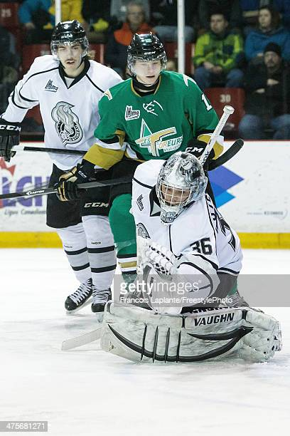 Robert Steeves of the Gatineau Olympiques makes a glove save as MarcOlivier CrevierMorin defends against Julien Gauthier the ValD'Or Foreurs on...