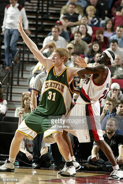 Robert Swift of the Seattle SuperSonics looks for the ball as Darius Miles of the Portland Trail Blazers defends on October 13 2004 at the Rose...