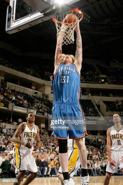 Robert Swift the Oklahoma City Thunder drives past Brandon Rush and Jeff Foster of the Indiana Pacers at Conseco Fieldhouse on November 10 2008 in...