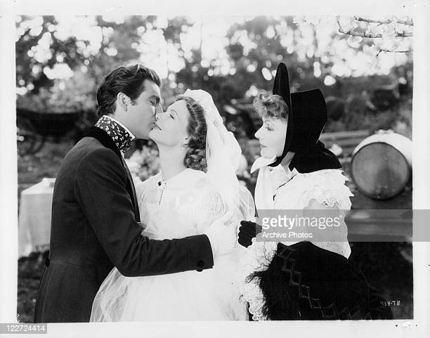 Robert Taylor kissing bride Elizabeth Allan while Greta Garbo watches on in a scene from the film 'Camille' 1936