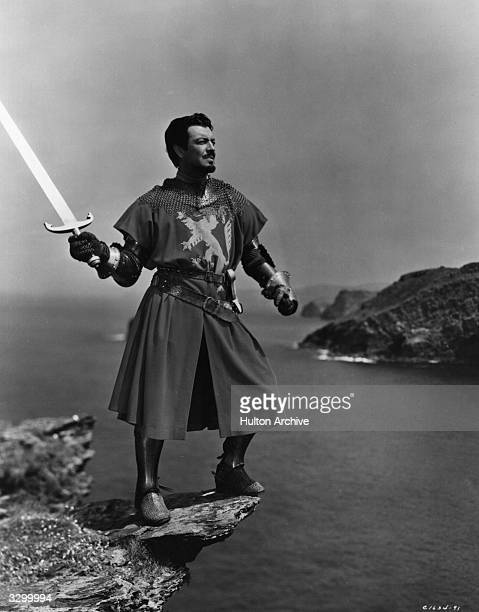 Robert Taylor the stage name of Spangler Arlington Brugh plays the part of Lancelot who is about to throw Excalibur the sword of King Arthur into the...
