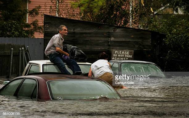 Robert Termier, age 66, and Ruth Ann Lewis, age 49, hang onto car rooftops as they wait to be evacuated by helicopter from their home in Mid Town New...