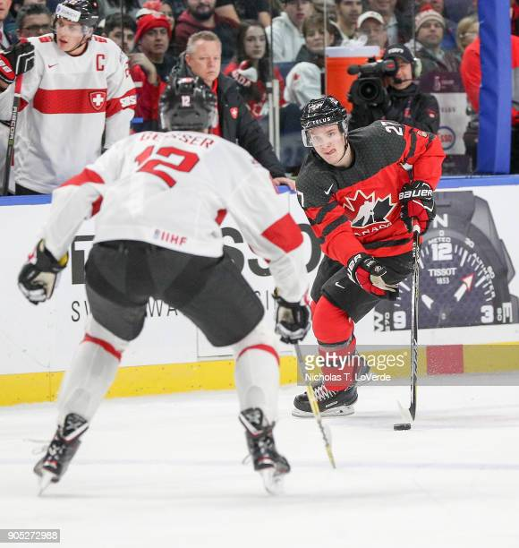 Robert Thomas of Canada skates the puck up ice with Tobias Geisser of Switzerland defending the play during the first period of play in the...