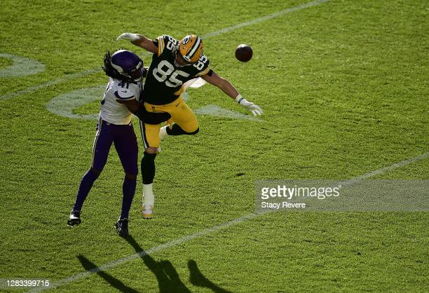 Robert Tonyan of the Green Bay Packers is defended by Anthony Harris of the Minnesota Vikings during the fourth quarter of the game at Lambeau Field...