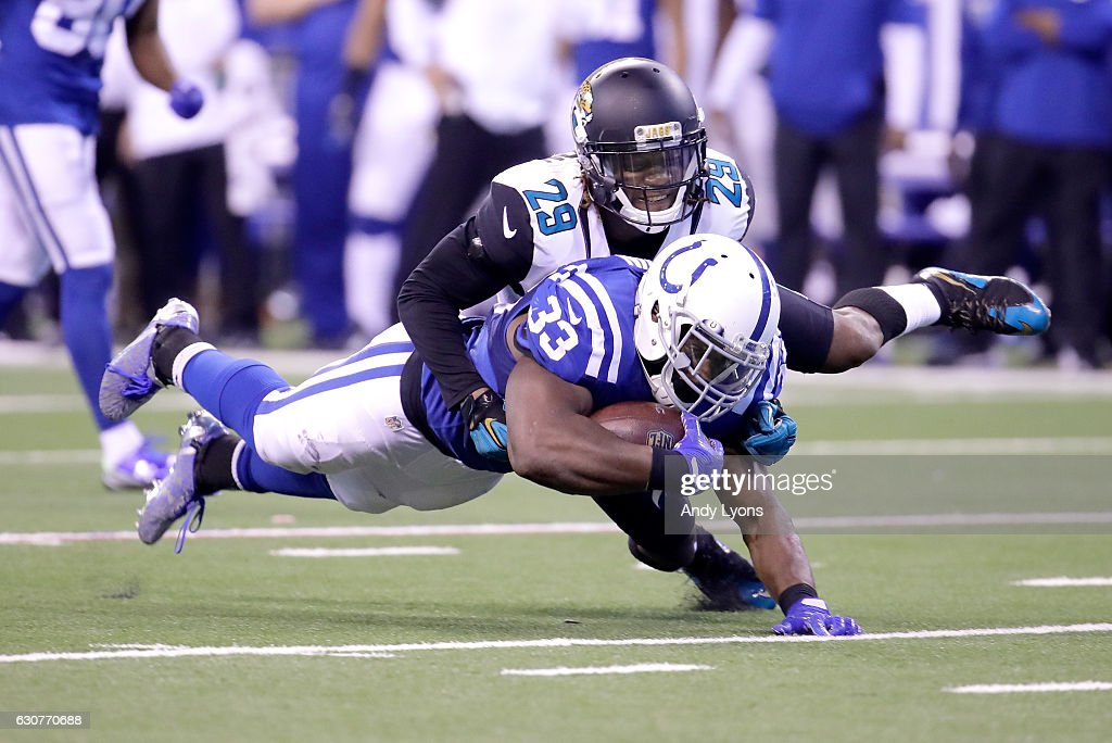 Robert Turbin #33 of the Indianapolis Colts dives for extra yardage while defended by Josh Johnson #29 of the Jacksonville Jaguars at Lucas Oil Stadium on January 1, 2017 in Indianapolis, Indiana.