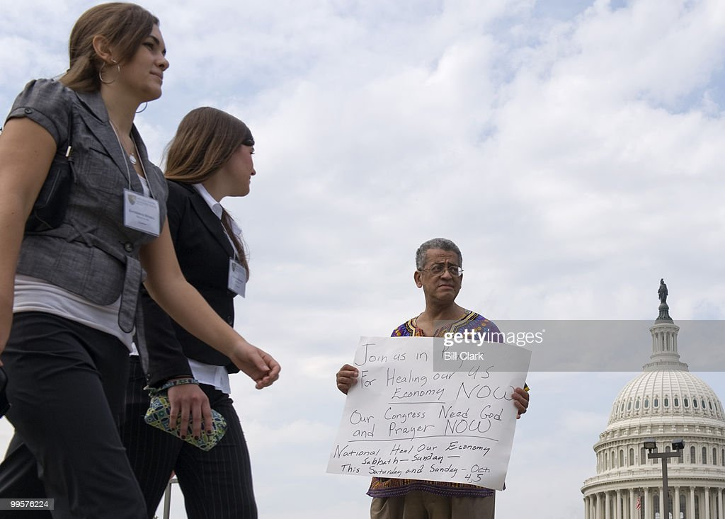 Robert Twyman, of the Pray at the Pump Movement, pleads with pedestrians to pray for the economy as he stands outside of the Supreme Court on Wednesday, Oct. 1, 2008.