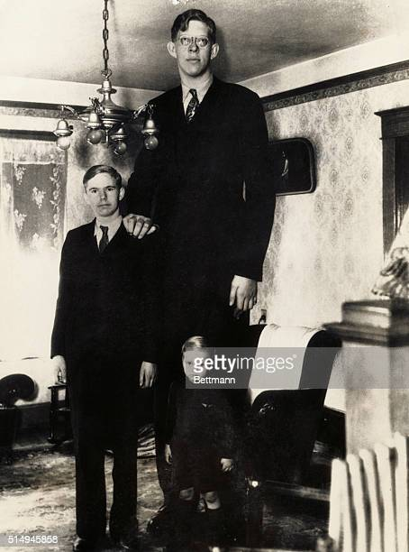 Robert Wadlow 8 feet 5 3/4 inches tall at age 18 standing besides his brothers Eugene age 14 and Harold age 3 1/2 at their home in Alton Illinois