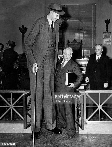 Robert Wadlow, the worlds tallest man, standing in a courtroom with his attorney during a recent libel case.