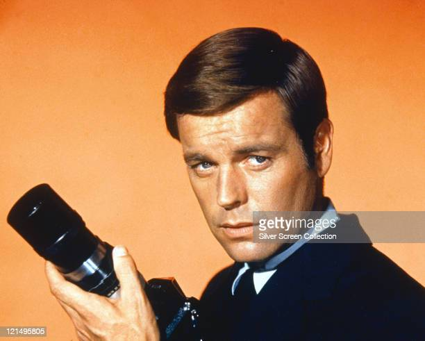 Robert Wagner, US actor, holding a camera with a telephoto lens in a studio portrait, against an orange background, issued as publicity for the US...
