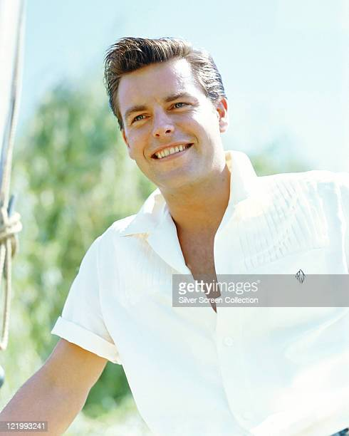 Robert Wagner US actor smiling and wearing a shortsleeved white polo shirt with the neck unbuttoned circa 1955