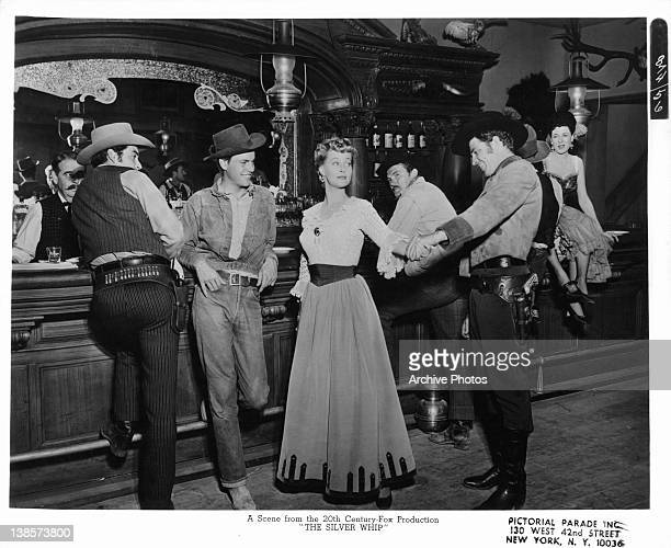 Robert Wagner watches as other men check out Lola Albright in the saloon in a scene from the film 'The Silver Whip' 1953