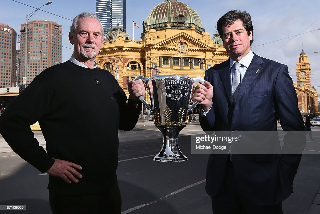 Robert Walls, former premiership coach for the Carlton Blues, and AFL CEO Gillon McLachlan (R) pose with the AFL Premiership Cup in front of the iconic Flinders Street Station during the 2015 AFL Finals Series launch at Federation Square on September 7, 2015 in Melbourne, Australia.