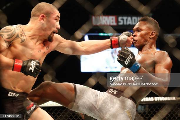 Robert Whittaker of Australia punches Israel Adesanya of New Zealand during the middleweight title bout of the UFC 243 fight night in Melbourne on...