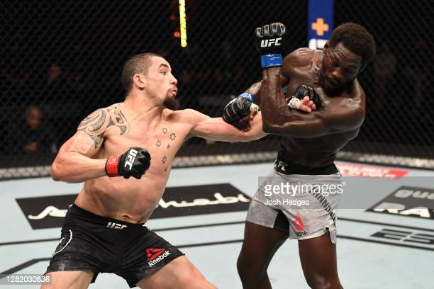 Robert Whittaker of Australia punches Jared Cannonier in their middleweight bout during the UFC 254 event on October 25, 2020 on UFC Fight Island,...