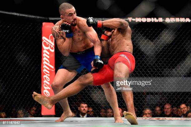 Robert Whittaker of New Zealand knocks down Yoel Romero of Cuba in their interim UFC middleweight championship bout during the UFC 213 event at the...