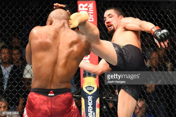 Robert Whittaker of New Zealand lands a head kick against Yoel Romero of Cuba in their middleweight fight during the UFC 225 event at the United...