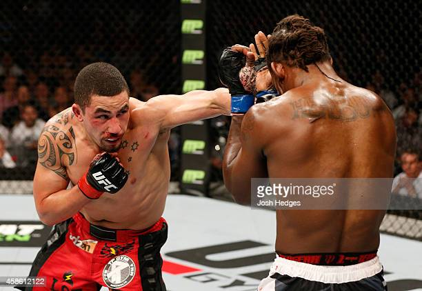 Robert Whittaker of New Zealand punches Clint Hester of the United States in their middleweight bout during the UFC Fight Night event inside...