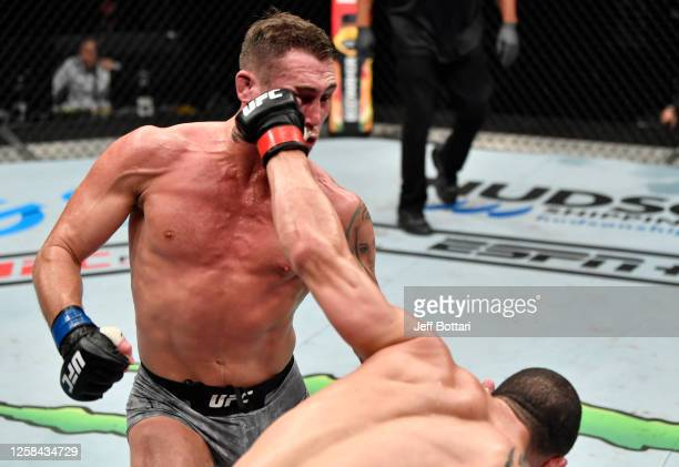 Robert Whittaker of New Zealand punches Darren Till of England in their middleweight fight during the UFC Fight Night event inside Flash Forum on UFC...