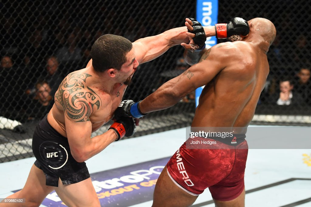 Robert Whittaker of New Zealand punches Yoel Romero of Cuba in their middleweight fight during the UFC 225 event at the United Center on June 9, 2018 in Chicago, Illinois.