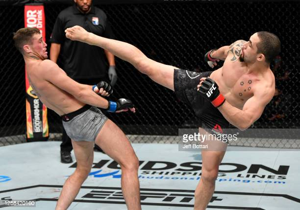 Robert Whittaker of New Zealand throws a kick against Darren Till of England in their middleweight fight during the UFC Fight Night event inside...