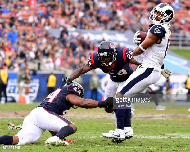 Robert Woods of the Los Angeles Rams eludes the tackle of Johnathan Joseph and Jelani Jenkins of the Houston Texans at Los Angeles Memorial Coliseum...