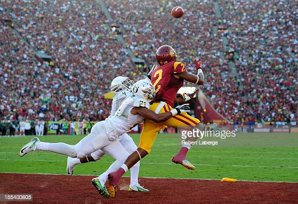 Robert Woods of the USC Trojans scores a touchdown in the first half as Avery Patterson and Erick Dargan of the Oregon Ducks tackle him at Los...