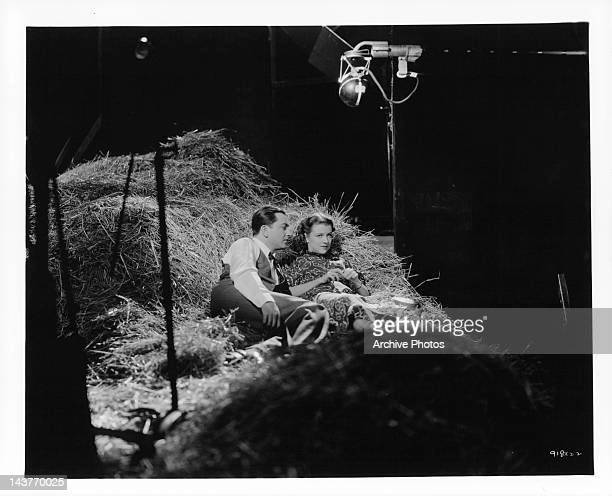 Robert Young and Betty Furness being filmed on a haystack in 'The Three Wise Guys', 1936.
